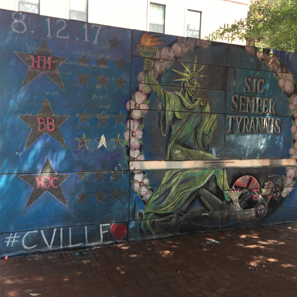 "This mural appeared on the downtown mall's Freedom of Speech wall following the events on August 12, 2017. It depicts: the initials of the three individuals who died on August 12 (Heather Heyer and Virginia State Police officers Lt. H. Jay Cullen and Trooper Berke M.M. Bates) and the Statue of Liberty vanquishing a Nazi alongside the Virginia state motto, ""Sic Semper Tyrannis."""