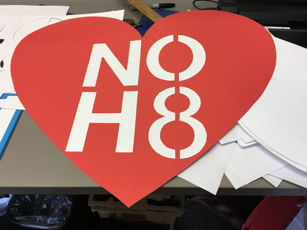 "Anonymous, ""Making signs"" —a red and white sign in the shape of a heart saying ""No H8"""
