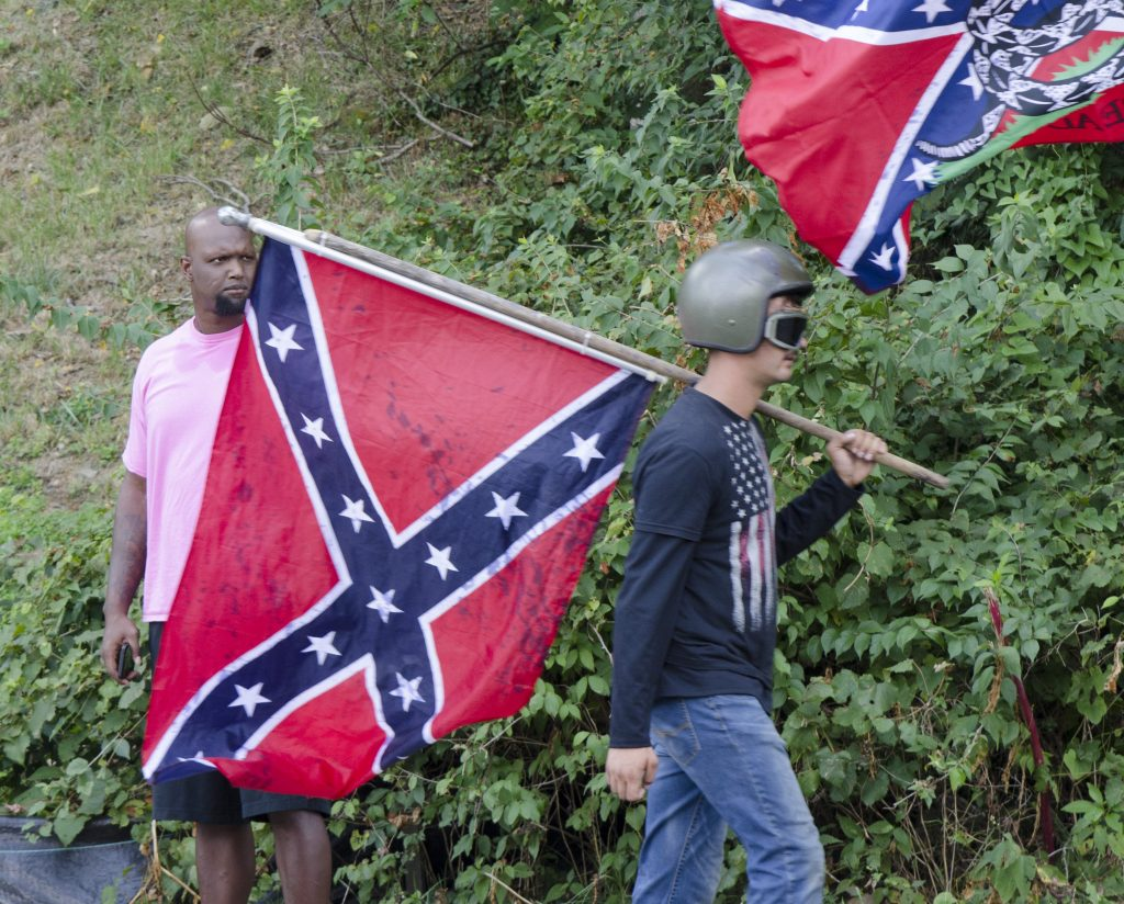 "Photo by Gary Powell titled ""McIntire Street."" An African American man looks on as a white man carrying a Confederate flag walks past"