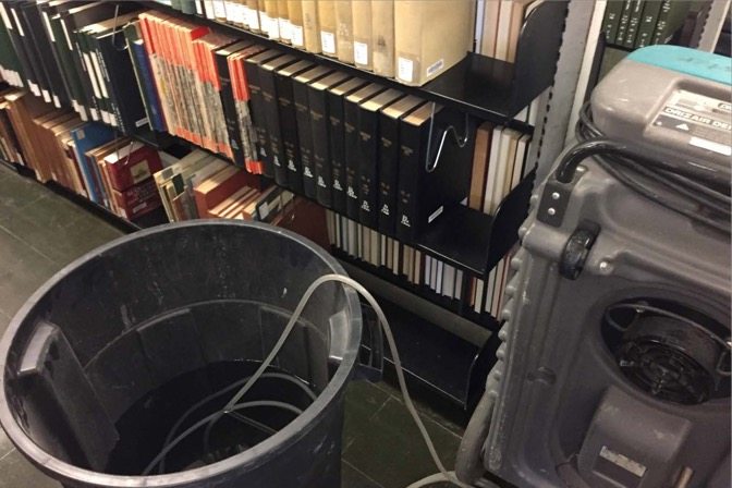 An open trash can with water hoses feeding into it beside a shelf of books in the stacks